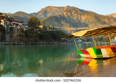 Colorful boat in green and clean Ganges River at sunset in Rishikesh, Uttarakhand, India
