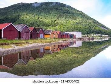 Colorful boathouses in the haven of Stordal with beautiful reflections and the mountains in background. Stordal is a small town at the Stordfjord (Norway).