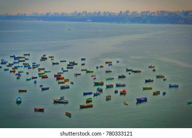 Colorful boats in the bay with the city of Lima in the background.