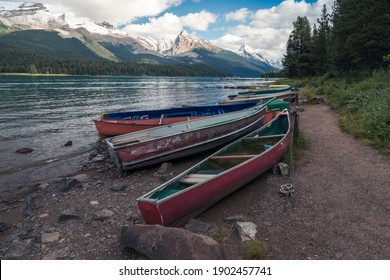 Colorful boats by Maligne lake, with Samson peak, Maligne mountain and Mount Paul in the background. Summer in Maligne valley of Jasper National Park, Alberta, Canada.