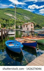 colorful boats in the fishing harbor in Nago-Torbole, Garda lake, Trentino-Alto Adige region, Italy