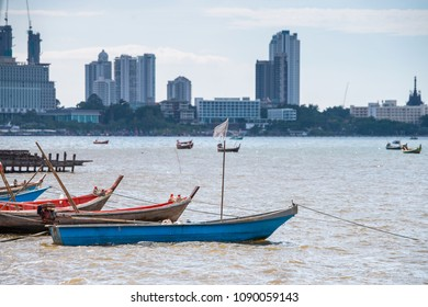 Colorful boats near the shore with a contrasting background of the city