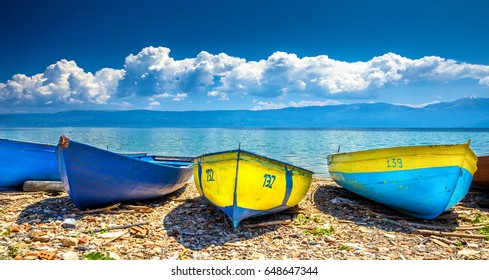 Colorful boats on the beach at the lake of Ohrid with cloudy sky, Albania.