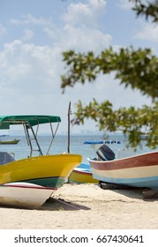 Colorful boats on the beach. Turquoise water of the Caribbean sea in the background. White sand beach. Some tree branches in front out of focus.
