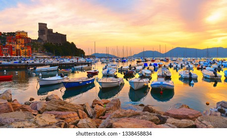 colorful boats and seascape, old castle against  cloudy warm sky with sunset  in Lerici in Liguria, Italy