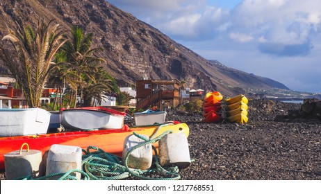 """Colorful boats and stacked surfboards on the beach of """"El Remo"""" on La Palma.In the background mountains and a blue sky, in the foreground green ropes and fastening ropes."""