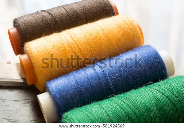Colorful Bobbins on Wooden Table. Sewing Threads of Different Colors Close-up Image