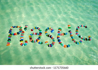 Colorful bottle caps spell out the word 'plastic' floating on the sea. A reminder for people to reduce, reuse and recycle.