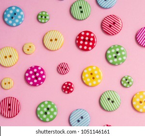 Colorful bottons on pink background