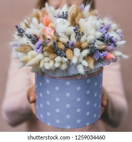 Colorful bouquet of different dried flowers deadwood flowers in the hands of a florist woman. Rustic flower background. Craft bouquet of flowers.