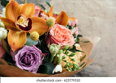 Colorful  bouquet of different fresh flowers. Bunch of orchids, roses, freesia and eucalyptus leaves. Rustic flower background. Close up