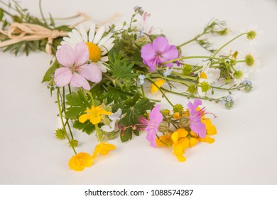 A colorful bouquet of freshly picked wild flowers from a natural meadow and garden tied with a natural decorative raffia string. Presented on a table outdoors on a white surface.