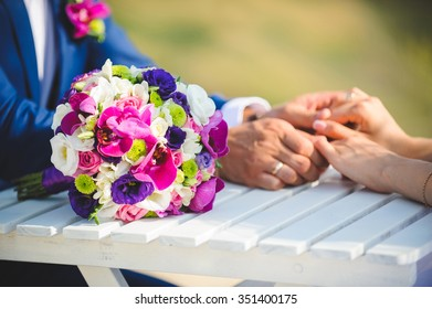 colorful bouquet on table with bride and groom