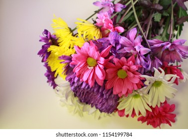 Colorful bouquet with pink, yellow, purple, and white flowers lying on a white background