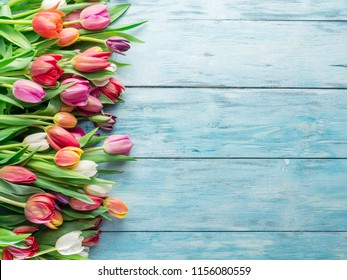 Colorful  bouquet of tulips on blue wooden background.  Top view.