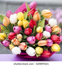 Colorful bouquet of white, pink, yellow and red tulips lying on the gift box. Spring background.