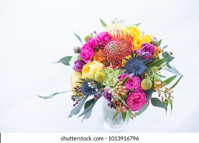 Colorful bouquet of yellow, coral and rose roses, blue eringium, red leucospermum, orange asclepia, eucalyptus and greenery