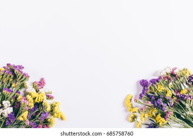 Colorful bouquets of flowers lie on a white background, top view