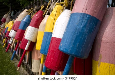 Colorful bouys hang on a woodem fence in Coastal Maine.