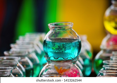 colorful bowls of water are part of a carnival game. toss in balls and win a gold fish