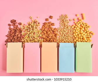 Colorful boxes of cornflakes or cereal of different types on pink background, top view