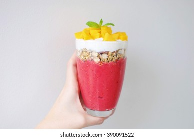Colorful breakfast parfait with smoothie, granola, skyr and mango