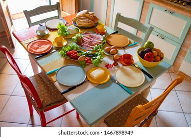 colorful breakfast table full with food butter, tomatoes, ham, bread in a bright kitchen in a house in Tuscany in Italy
