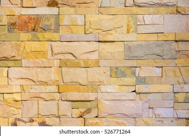 Colorful brick wall in yellow pastel tone. The picture can be used as a beautiful texture for vintage buildings.
