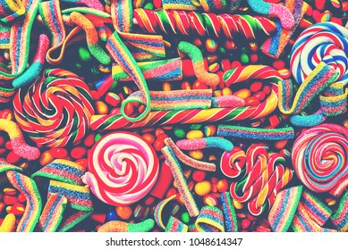 Colorful bright assorted  candy canes and rainbow colored spiral lollipops  with scattered marmalade, jellybeans and different colored round candy. Top view. Candy background.