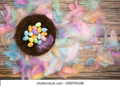 Colorful bright easter eggs in bird nest with Pastel colored feathers and wooden background texture top view, Copy Space, Spring, Easter Holliday, greeting card concept colorful design