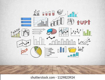 Colorful and bright infographics with bar charts and diagrams, business growth icons drawn on a concrete wall in a room with a wooden floor. Data representation concept