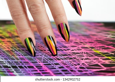 Colorful bright manicure with different sharp shape of nails framed with black lacquer.Nail art. Creative nail design on color background.