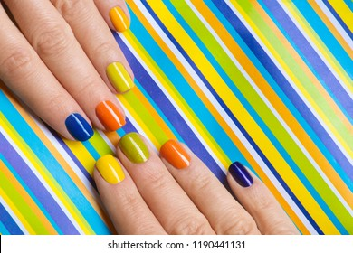 Colorful bright manicure with orange, blue, yellow nail Polish on striped background close-up.Nail art.