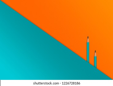 colorful bright orange and teal background, flat lay op paper and two pencils