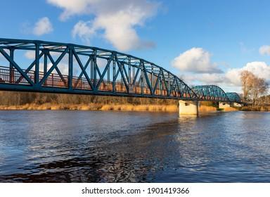 Colorful, bright pedestrian bridge across the river in the autumn. Latvia.