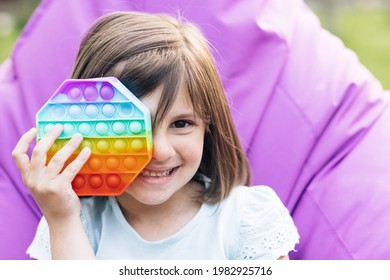 Colorful and bright pop it toy simple dimple. Trendy antistress sensory toy fidget push pop it and simple dimple in kid's hands. Close up of portrait little girl with a modern popit toy.