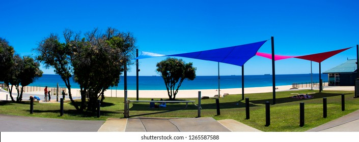 Colorful bright  red and blue shade sails provide coolness on the grassy  green lawns during the hot summer  at Ocean Beach Bunbury, Western Australia after a swim in the sparkling blue Indian Ocean.