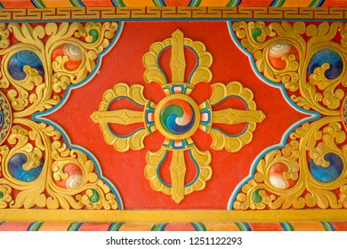 a colorful bright red yellow blue Buddhist vajra image on the wall of the temple. sacred images