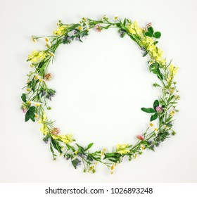 Colorful bright round frame made of summer meadow flowers on white background. Flay lay, top view with copy space