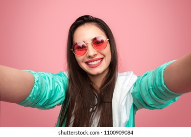 Colorful bright woman in sunglasses taking selfie with happy smile on pink background.