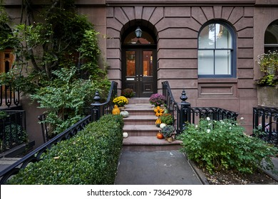 a colorful brownstone building with pumpkins on the steps