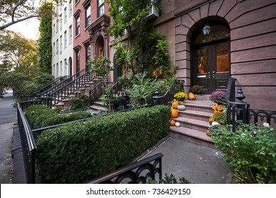 a colorful brownstone building with pumpkins on the steps in an iconic neighborhood of Manhattan, New York City.