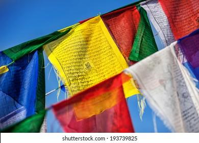 Colorful Buddhist prayer flags at blue sky near Bodhnath stupa in Kathmandu valley, Nepal