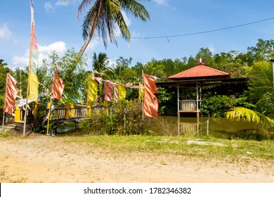 Colorful Buddhist prayer flags, pond and temple among green tropical nature in Wei Tuo Fa Gong Buddhist Temple in Pulau Ubin Island, Singapore.
