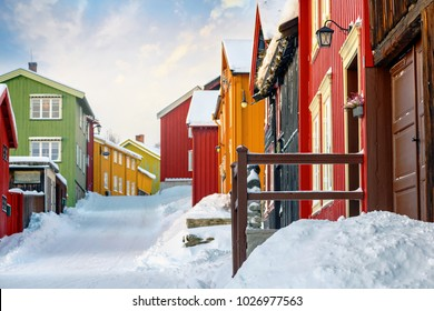 Colorful building facades at a street covered in snow during winter in the city of Roros. Very vivid colors.