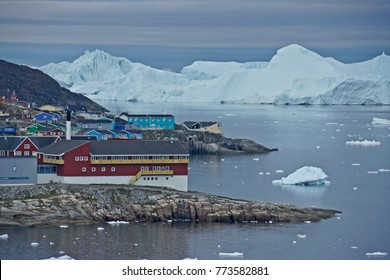 Colorful buildings of Illulissat, West Greenland, with icebergs in the background