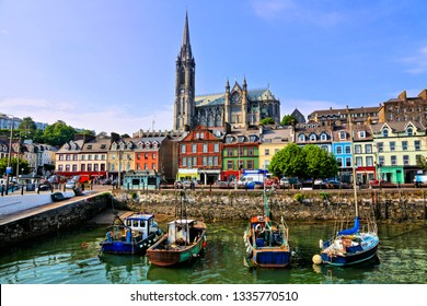 Colorful buildings and old boats with cathedral in background in the harbor of Cobh, County Cork, Ireland