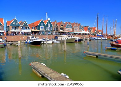 Colorful buildings and small vessels inside the harbor of Volendam, Holland