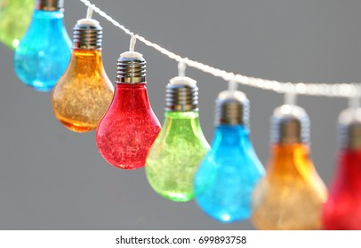 Colorful bulbs hang on string outdoor