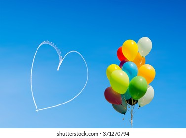 Colorful bunch of balloons and romantic heart written in the sky by an aircraft, with copy space
